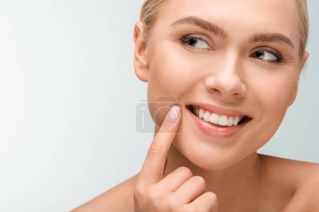 Photo pour Happy woman pointing with finger at face isolated on white - image libre de droit
