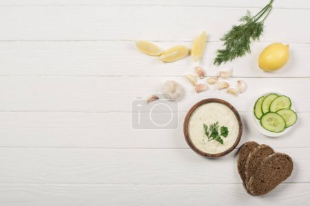 Top view of tzatziki sauce with ingredients and bread on white wooden background