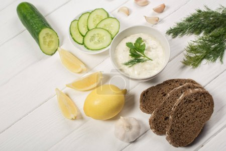 Tasty tzatziki sauce with fresh ingredients and bread on white wooden background