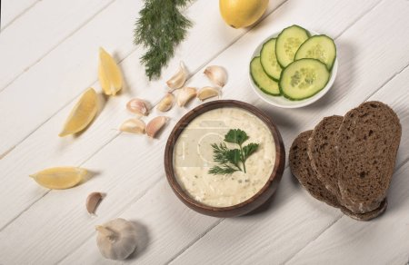 Photo for Top view of tzatziki sauce with greenery, cucumber and lemon on white wooden background - Royalty Free Image