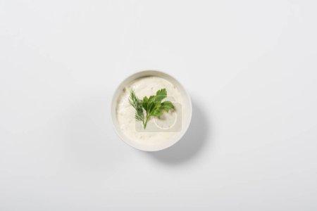 Draufsicht auf leckere Tzatziki-Sauce mit Grün auf weißem Hintergrund
