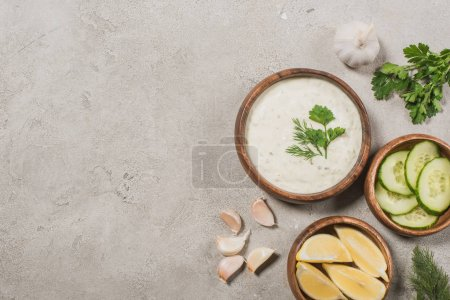 Photo for Top view of tzatziki sauce with ingredients on stone surface - Royalty Free Image