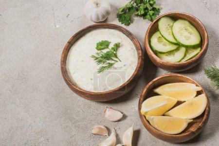 leckere Tzatziki-Sauce mit Zitrone, Gurke und Knoblauch auf Steinhintergrund