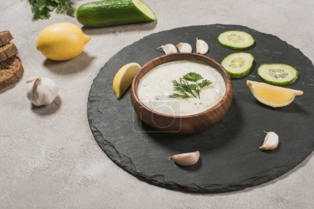 Photo for Gourmet tzatziki sauce with raw ingredients on stone surface - Royalty Free Image
