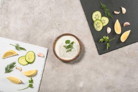 Draufsicht auf Tzatziki-Sauce mit frischen Zutaten auf Brettern auf Steinhintergrund