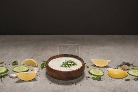 leckere Tzatziki-Sauce in Holzschüssel mit Zutaten und Gewürzen auf Steinoberfläche auf schwarzem Hintergrund