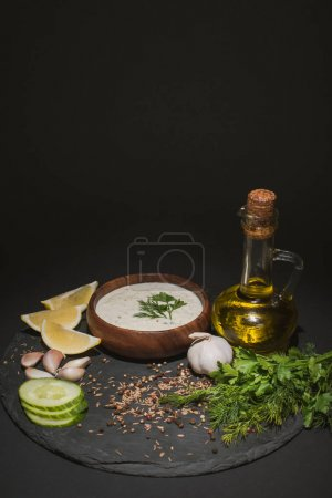 Photo for Tzatziki sauce with organic ingredients, spices and olive oil on dark board on black background - Royalty Free Image