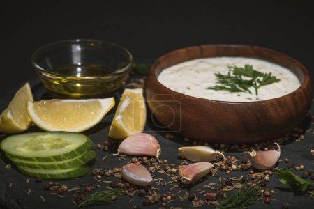 selektiver Fokus der Tzatziki-Sauce mit Gewürzen und Zutaten auf schwarzem Hintergrund
