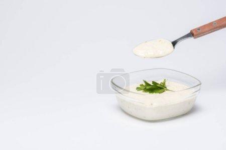 traditionelle griechische Tzatziki-Sauce mit Löffel auf weißem Hintergrund