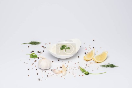 Photo for Tzatziki sauce in bowl with ingredients and spices on white background - Royalty Free Image