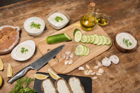 Photo pour Ingrédients frais à l'huile d'olive et sauce tzatziki dans des bols sur une table en bois - image libre de droit