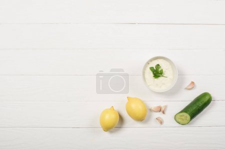 Photo for Top view of tzatziki sauce with lemons, cucumber and garlic on white wooden background - Royalty Free Image