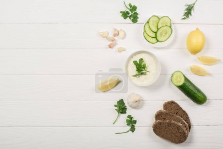 Photo for Top view of tzatziki sauce ingredients, greens and bread on white wooden background - Royalty Free Image