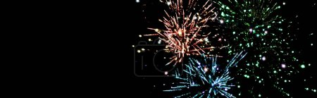 Photo pour Panoramic shot of blue, green and orange festive fireworks in dark night sky, isolated on black - image libre de droit