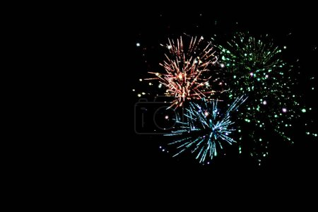 Photo for Blue, green and orange traditional fireworks in dark night sky, isolated on black - Royalty Free Image