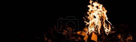 Foto de Tiro panorámico de llama y troncos en el fuego del campamento en la oscuridad en la noche - Imagen libre de derechos