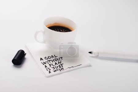 Photo for Coffee cup on paper napkin with goal without plan just wish inscription, and felt pen on white table - Royalty Free Image