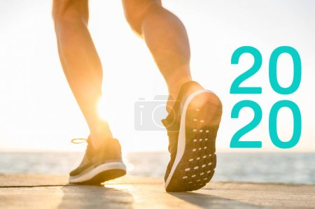 Photo pour Cropped view of runner in sneakers near 2020 lettering in sunshine - image libre de droit