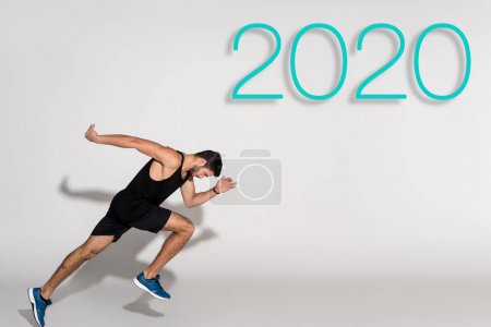 Photo for Side view of sportsman running on white background with 2020 lettering - Royalty Free Image