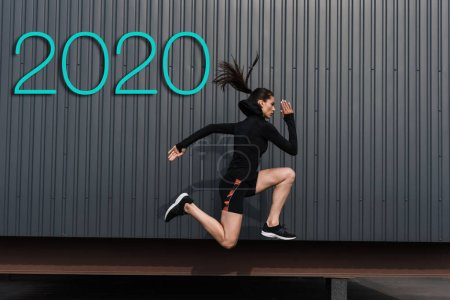 Photo for Side view of asian sportswoman running near wall with 2020 lettering - Royalty Free Image