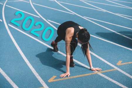 Photo for Young sportswoman standing in start positing on running track near 2020 lettering - Royalty Free Image