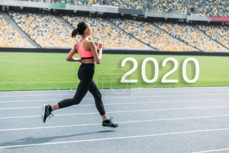 Photo for Young african american sportswoman running on stadium near 2020 lettering - Royalty Free Image