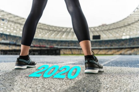 Photo for Cropped view of sportswoman standing on running track near 2020 lettering - Royalty Free Image