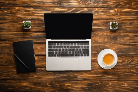 Photo pour Top view of laptop with blank screen, coffee cup, notebook and potted plants on wooden desk. - image libre de droit