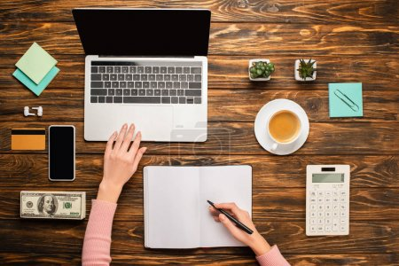 Photo for Cropped view of businesswoman writing in notebook near laptop, smartphone, coffee cup, credit card, money and calculator on wooden desk - Royalty Free Image