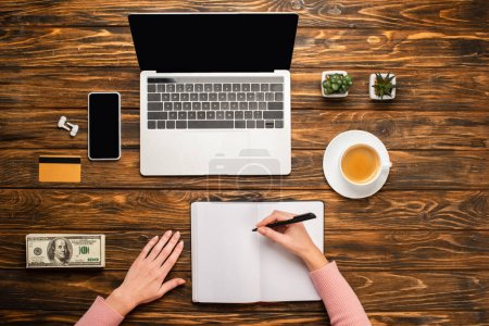 Photo for Cropped view of businesswoman writing in notebook near laptop, smartphone, coffee cup, credit card and dollar banknotes on wooden desk - Royalty Free Image