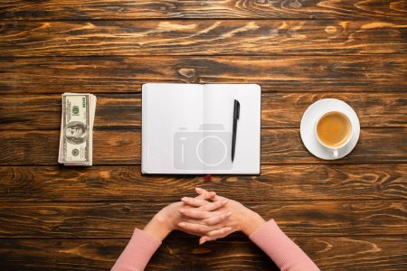 Photo for Cropped view of businesswoman stretching hands while preparing to write new year resolution near dollar banknotes and coffee cup on wooden desk - Royalty Free Image