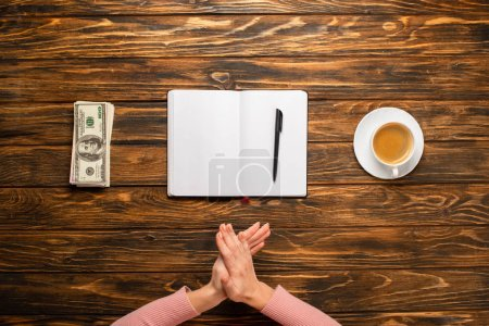 Photo for Cropped view of businesswoman rubbing hands while preparing to write new year resolution near dollar banknotes and coffee cup on wooden desk - Royalty Free Image