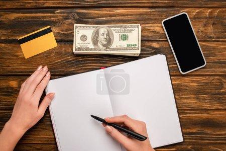 Photo pour Vue d'une femme d'affaires écrivant dans un cahier vierge, un téléphone intelligent, des billets de banque en dollars et une carte de crédit sur un bureau en bois - image libre de droit