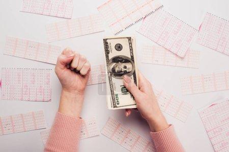 Photo pour Vue recadrée de la femme montrant le geste gagnant tout en tenant des billets en dollars près des billets de loterie dispersés sur la table blanche - image libre de droit