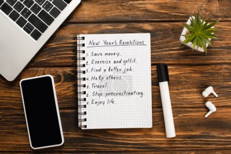 Photo pour Notebook with list of new years resolutions, felt-tip pen, laptop, smartphone, potted plant and wireless earphones on wooden desk - image libre de droit