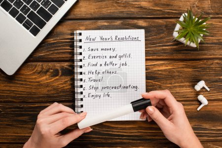 Photo for Cropped view of businesswoman holding felt-tip pen near notebook with list of new years resolutions near laptop, potted plant and wireless earphones on wooden desk - Royalty Free Image