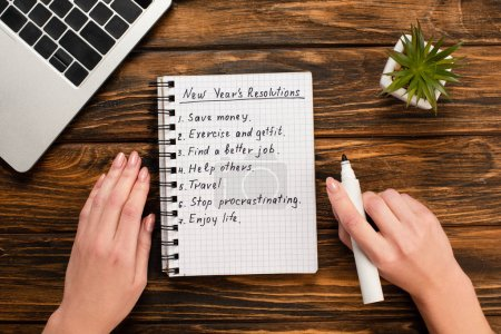 Photo for Cropped view of businesswoman holding felt-tip pen near notebook with list of new years resolutions near laptop and potted plant on wooden desk - Royalty Free Image