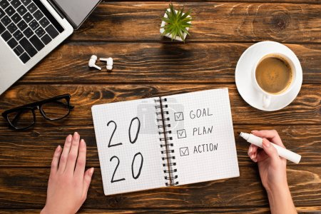 Photo for Cropped view of businesswoman holding felt-tip pen near notebook with 2020, goal, plan, action lettering near laptop, wireless earphones, coffee cup on wooden desk - Royalty Free Image