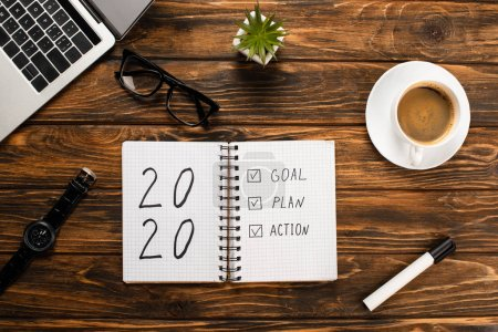 Photo for Notebook with 2020, goal, plan, action lettering, laptop, coffee cup, felt-tip pen, glasses, wristwatch and plant on wooden desk - Royalty Free Image
