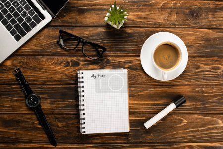 Photo for Notebook with my plan lettering, laptop, coffee cup, felt-tip pen, glasses, wristwatch and potted plant on wooden desk - Royalty Free Image