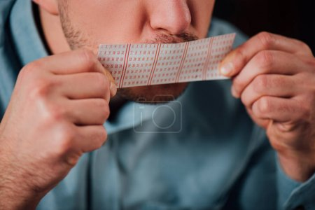 Photo for Cropped view of man kissing lottery ticket for luck - Royalty Free Image