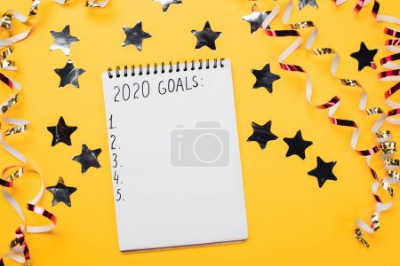 notebook with 2020 goals with empty numbered points near decorative, shiny stars and serpentine on yellow surface
