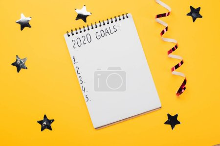 Photo pour Notebook with 2020 goals inscription with empty numbered points near decorative, shiny stars and serpentine on yellow surface - image libre de droit