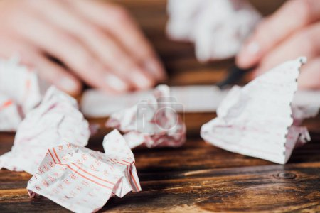 Photo for Selective focus of crumpled lottery tickets near gambler marking numbers in lottery card on wooden table - Royalty Free Image