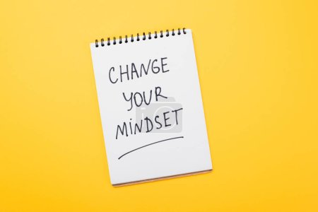 Photo for Top view of notebook with change your mindset inscription on yellow surface - Royalty Free Image