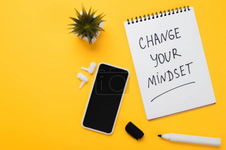 Photo for Notebook with change your mindset inscription near smartphone, wireless headphones, potted flower and felt-tip pen on yellow table - Royalty Free Image