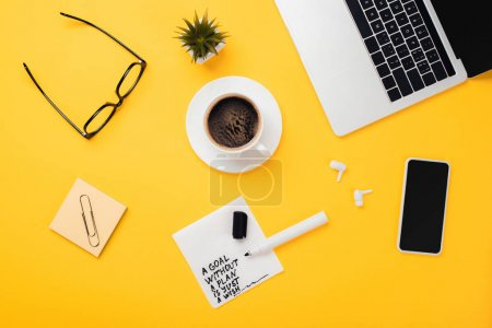 Photo for Paper napkin with goal without plan just wish inscription, felt-tip pen, laptop, smartphone, coffee cup, glasses, wireless headphones on yellow desk - Royalty Free Image