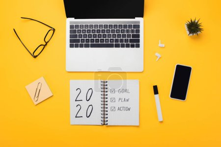 Photo for Notebook with 2020, goal, plan, action lettering near laptop, smartphone, wireless earphones and stationery on yellow desk - Royalty Free Image