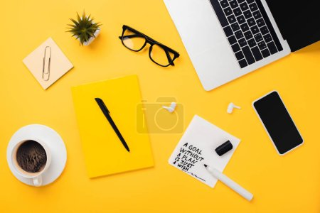 Photo for Paper napkin with goal without plan just wish inscription near coffee cup, glasses, flowerpot, digital devices and stationery on yellow desk - Royalty Free Image