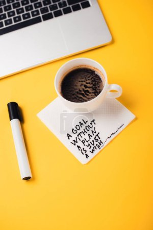 Photo for Coffee cup on paper napkin with goal without plan just wish inscription, notebook and felt-tip pen on yellow desk - Royalty Free Image